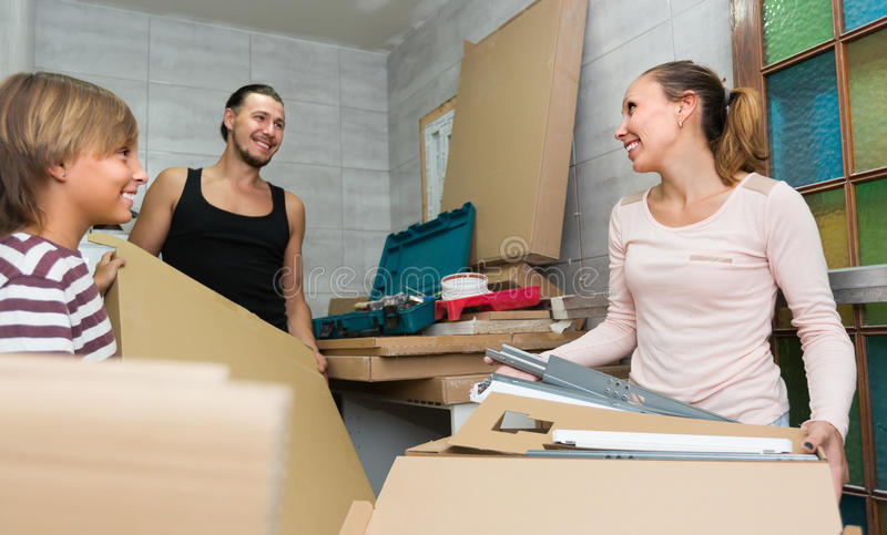 Family unpacking boxes with new furniture. Happy family unpacking boxes with new kitchen furniture. Focus on woman royalty free stock image