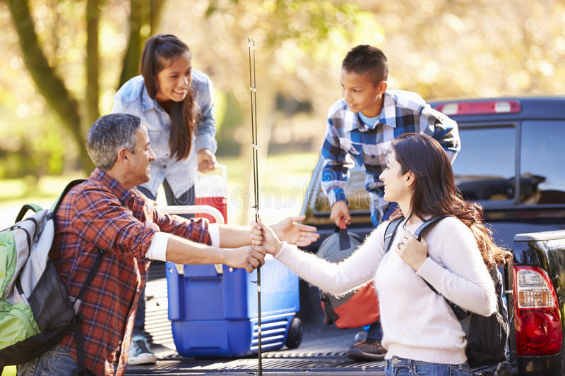 Family Unpacking Pick Up Truck On Camping Holiday stock image
