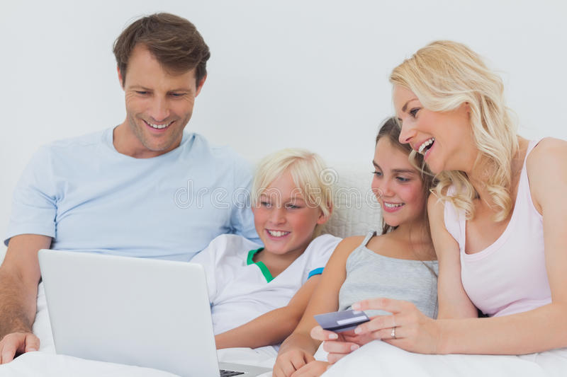 Download Family Using Computer And Credit Card In Bed Stock Image - Image: 31670151