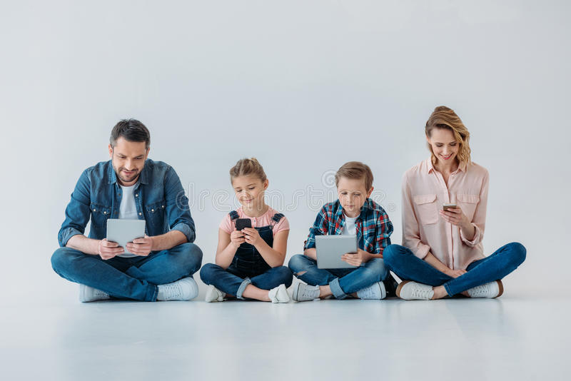 Family using digital devices while sitting on the floor. Happy family using digital devices while sitting on the floor royalty free stock photos