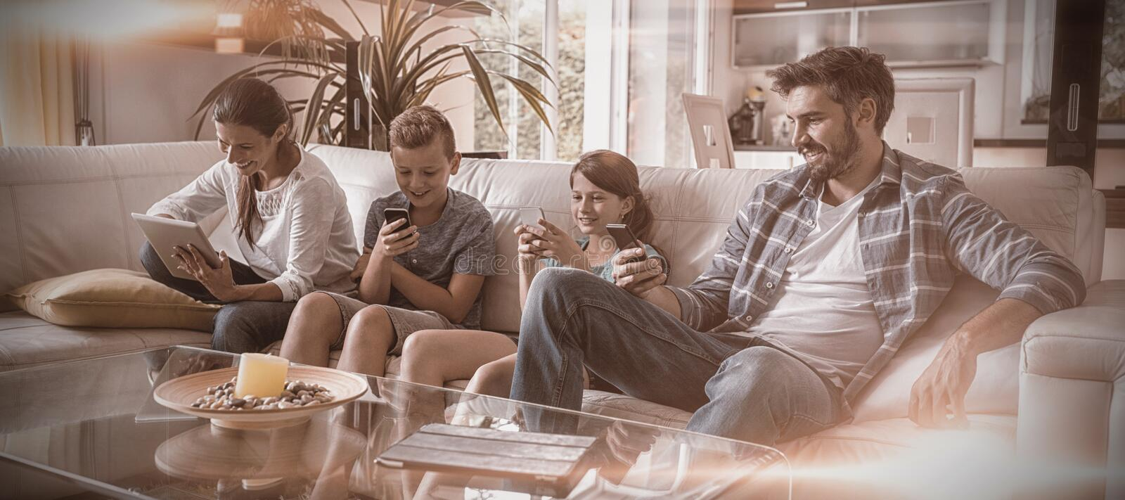 Family using digital tablet and mobile phone in living room stock images