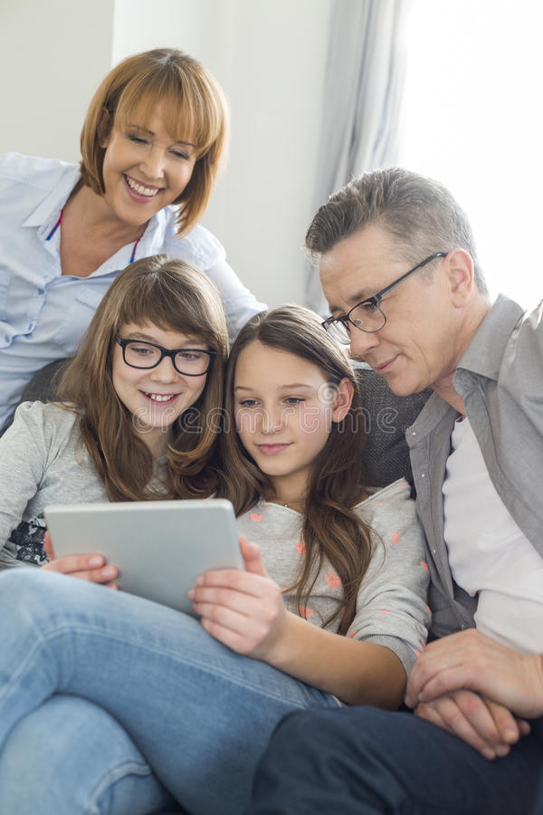 Family using digital tablet together in living room stock images