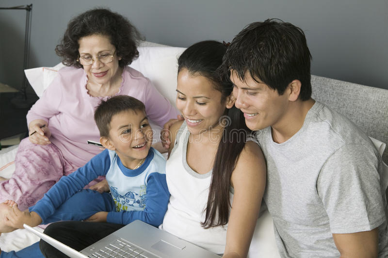 Family Using Laptop on Couch stock photos