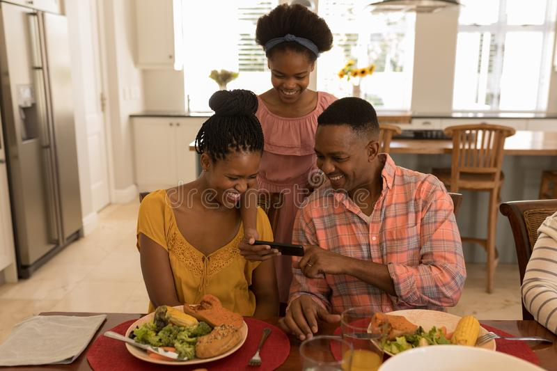 Family using mobile phone on dining table at home. Front view of African American happy parents looking at their daughters mobile phone while sitting at the royalty free stock photos