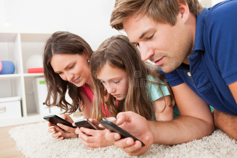Family using smart phones at home. Family using smart phones while lying on rug at home royalty free stock photos