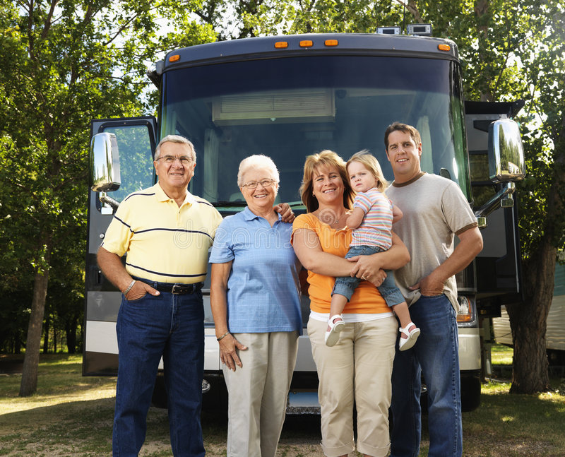 Family on vacation. Portrait of three generation Caucasian family standing in front of recreational vehicle smiling and looking at viewer stock photos