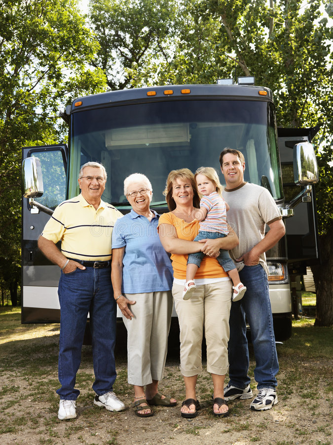 Family on vacation. Portrait of three generation Caucasian family standing in front of recreational vehicle smiling and looking at viewer royalty free stock images