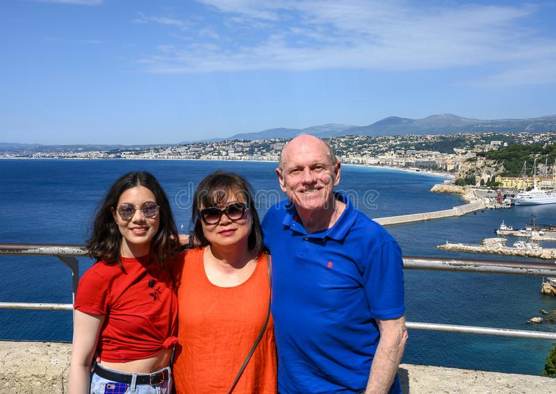 Family on vacation, in background Port of Nice also called  Lympia Port with a large white tourboat stock images