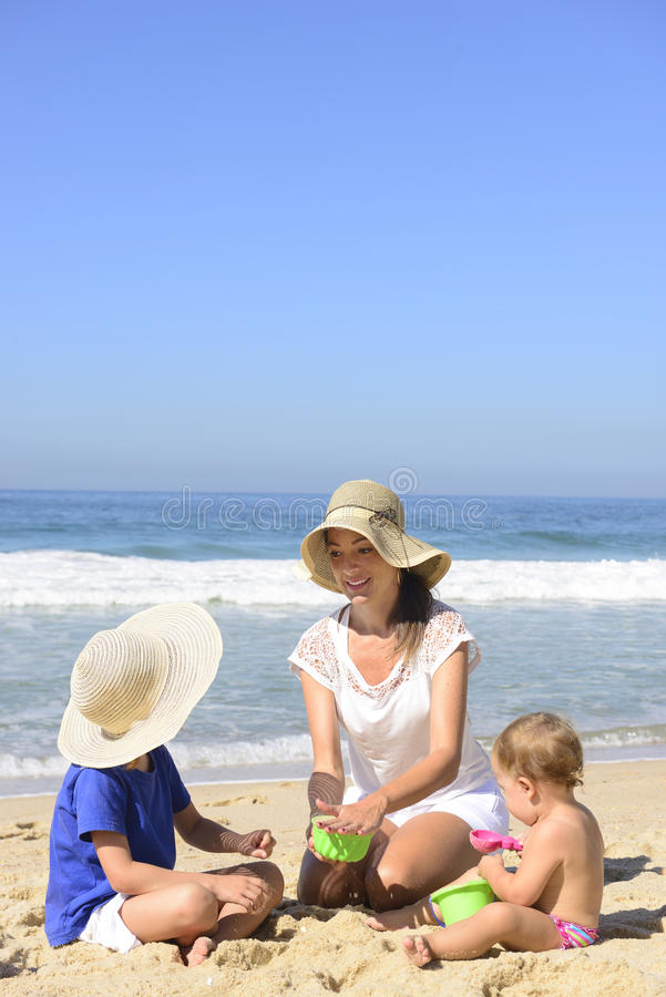 Family vacation on beach: Mother and kids. Playing in the sand royalty free stock photos