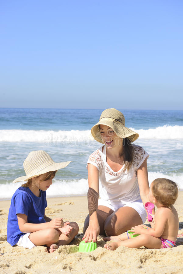 Family vacation on beach: Mother and kids. Playing in the sand stock photography