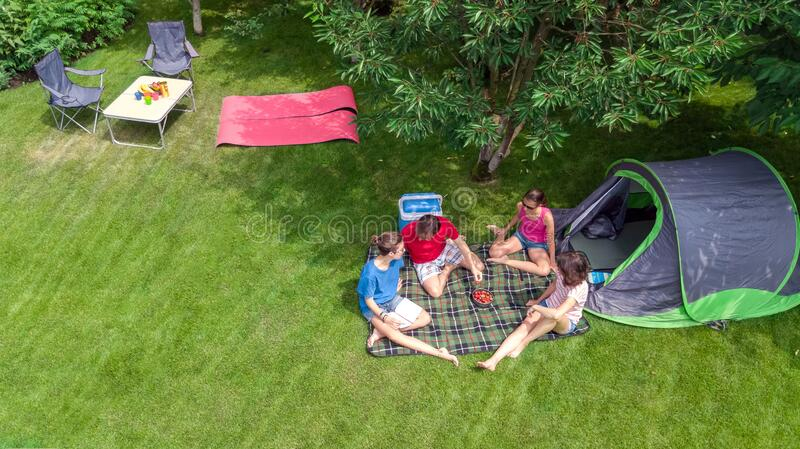 Family vacation in campsite aerial top view from above, parents and kids relax and have fun in park, tent and camping equipment stock photo
