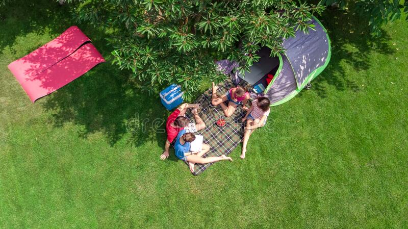 Family vacation in campsite aerial top view from above, parents and kids relax and have fun in park, tent and camping equipment royalty free stock image