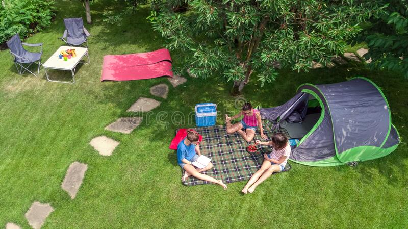 Family vacation in campsite aerial top view from above, parents and kids relax and have fun in park, tent and camping equipment royalty free stock photo