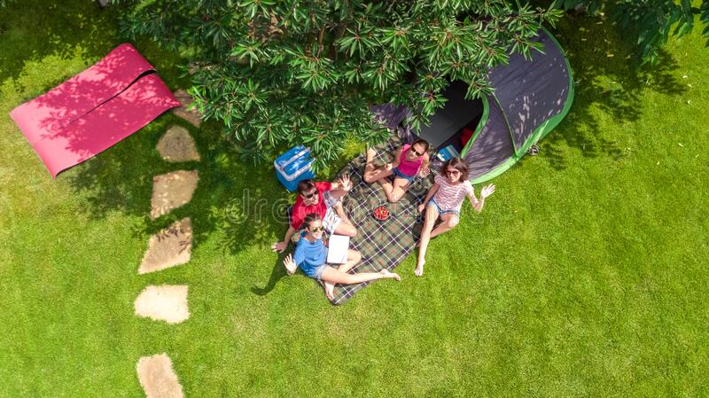 Family vacation in campsite aerial top view from above, parents and kids relax and have fun in park, tent and camping equipment royalty free stock photos