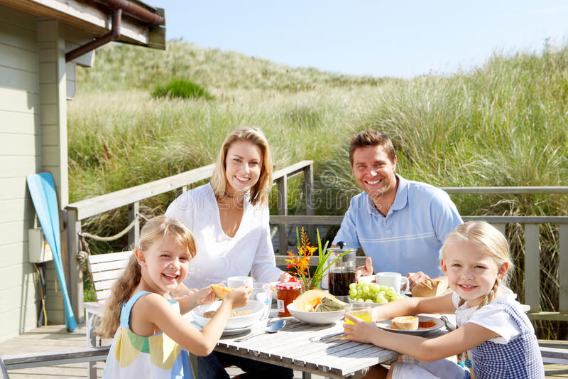 Family on vacation eating outdoors. On deck of beach hut stock photo