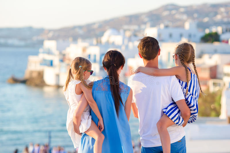 Family on vacation in Europe background the famous area in Mykonos. Family having fun outdoors on Mykonos streets royalty free stock photography