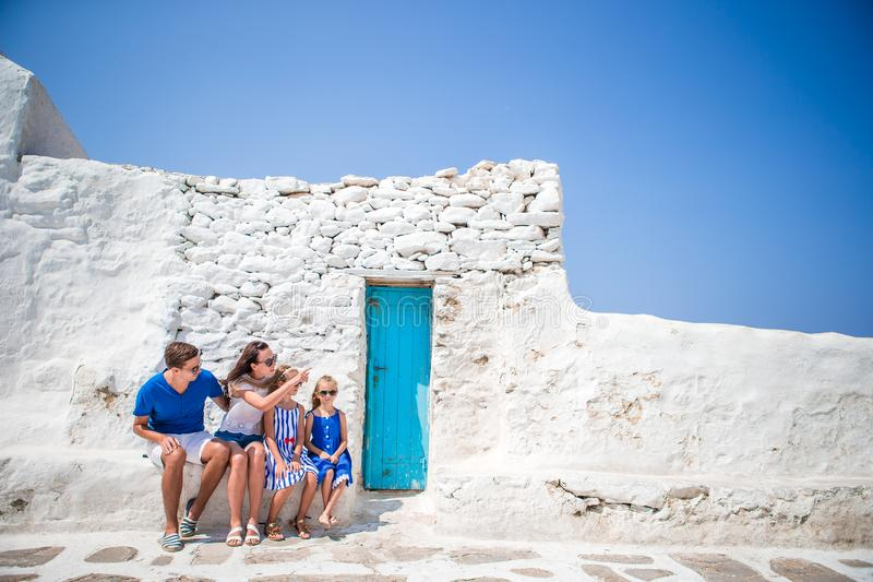 Family vacation in Europe. Parents and kids at street of typical greek traditional village with white walls and colorful stock photography
