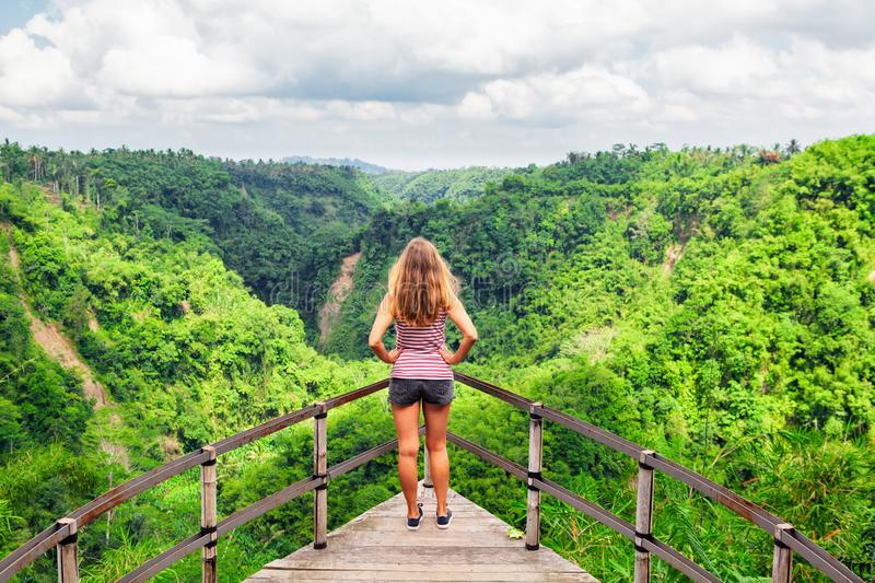 Woman stand on overhanging bridge on high cliff above jungle stock photos