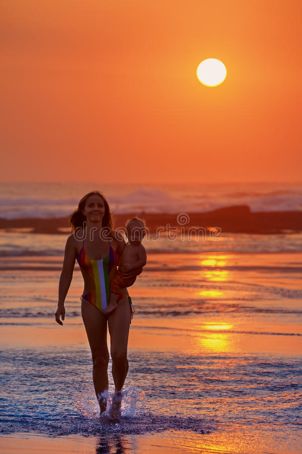Family vacation. Mother with child walk on sunset beach. Family swimming fun on black sand beach with sea surf. Happy mother walk with baby son on ocean beach royalty free stock images