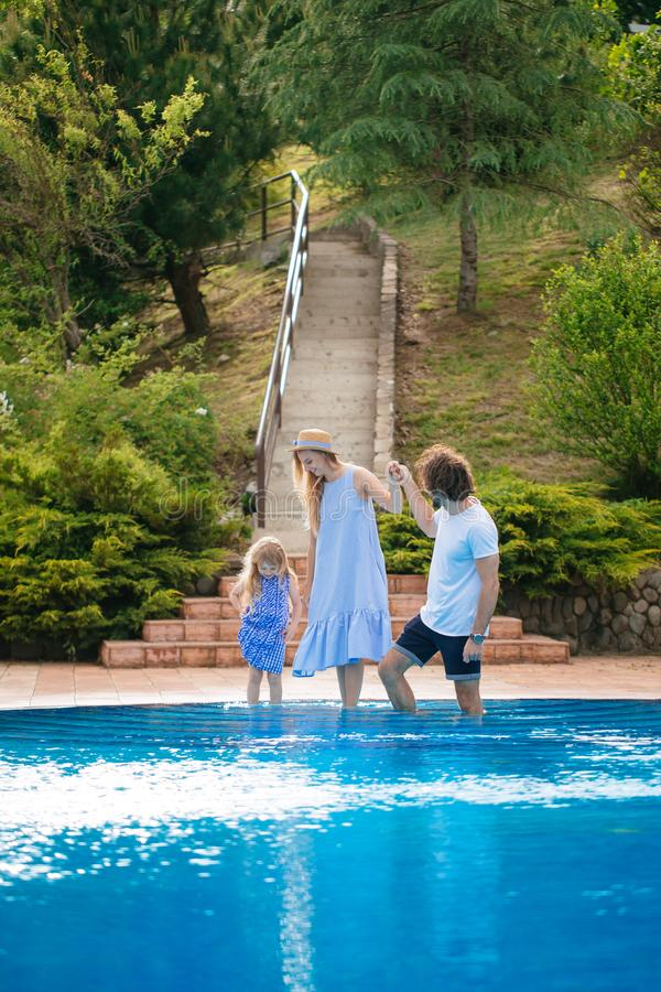 Family vacation in summer. Parents with kid having fun near swimming pool royalty free stock image