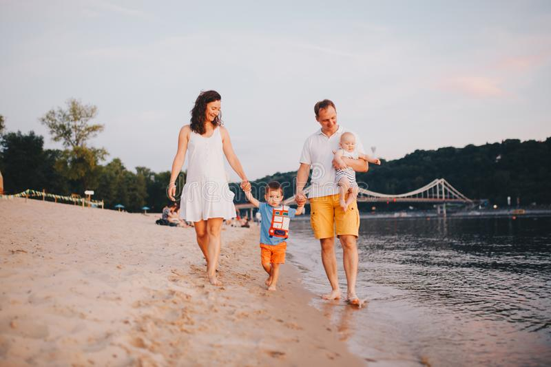 Family vacation in summer. Young Caucasian family foot walking barefoot sandy beach, shore river water. Dad mom holding hands two. Children, brothers. Big stock image