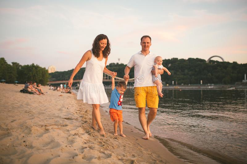 Family vacation in summer. Young Caucasian family foot walking barefoot sandy beach, shore river water. Dad mom holding hands two. Children, brothers. Big stock photos