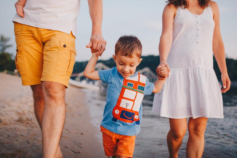 Family vacation in summer. Young Caucasian family foot walking barefoot sandy beach, shore river water. Dad mom holding hands two. Children, brothers. Big royalty free stock photo