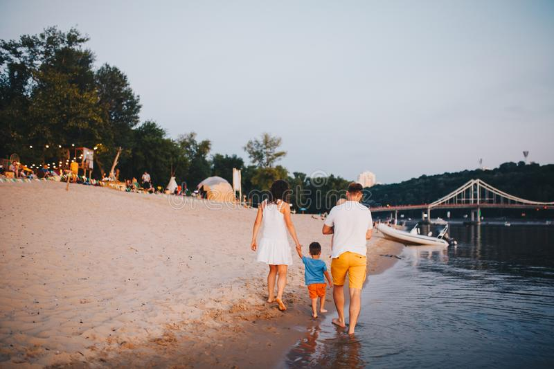 Family vacation in summer. Young Caucasian family foot walking barefoot sandy beach, shore river water. Dad mom holding hands two. Children, brothers. Big royalty free stock image