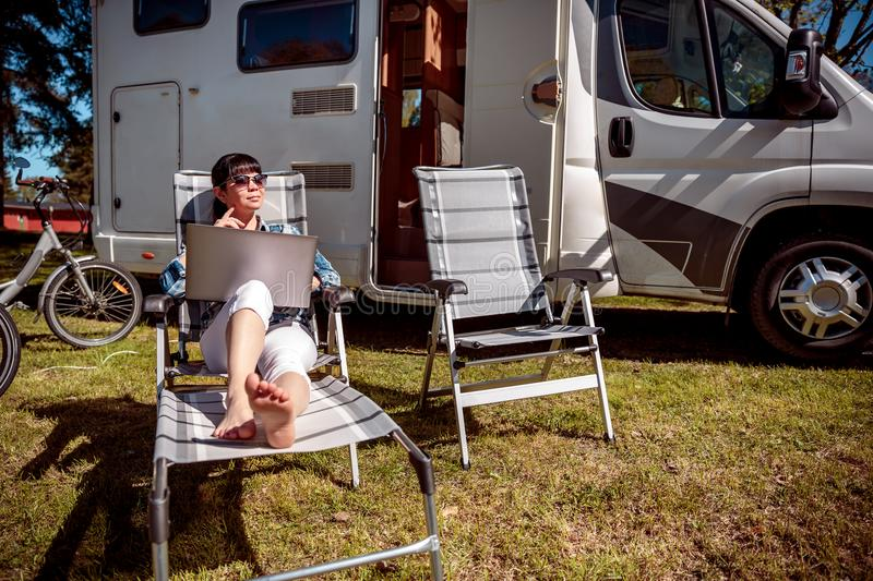 Family vacation travel, holiday trip in motorhome RV. Woman looking at the laptop near the camping . Caravan car Vacation. Family vacation travel, holiday trip royalty free stock photography