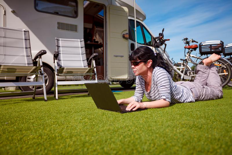 Family vacation travel, holiday trip in motorhome RV. Woman looking at the laptop near the camping . Caravan car Vacation. Family vacation travel, holiday trip royalty free stock photo