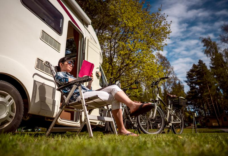 Family vacation travel, holiday trip in motorhome. Woman relaxes and reads a book near the camping . Caravan car Vacation. Family vacation travel, holiday trip royalty free stock images