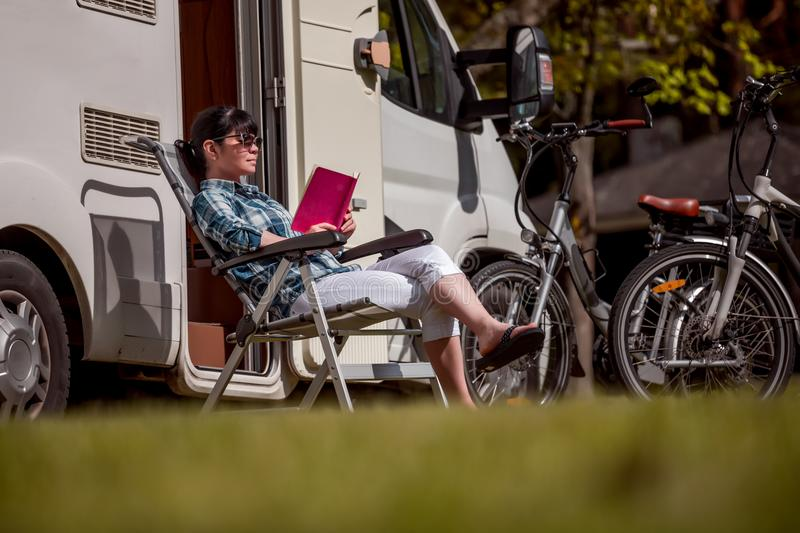 Family vacation travel, holiday trip in motorhome. Woman relaxes and reads a book near the camping . Caravan car Vacation. Family vacation travel, holiday trip stock photo