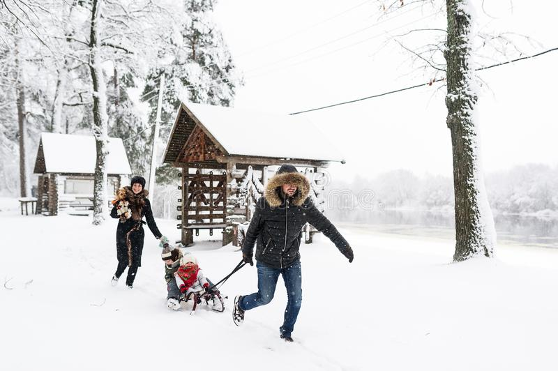 Family vacation on week-end outdoors. Little kids enjoy a sleigh ride. Child sledding.  stock photography