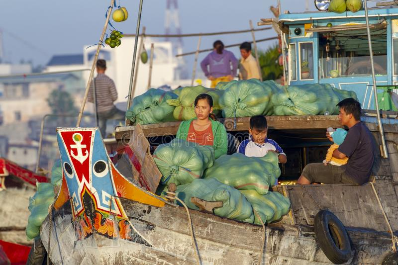 Family of vendors  in boat selling melons in floating market  on Mekong River in Vietnam royalty free stock photography