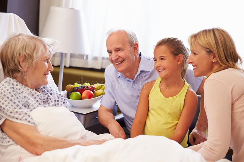 Family Visit To Grandmother In Hospital Bed royalty free stock image