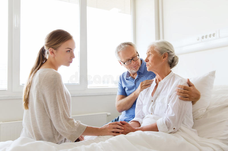 Family visiting ill senior woman at hospital. Medicine, support, family health care and people concept - senior men and young women visiting and cheering her ill stock photos