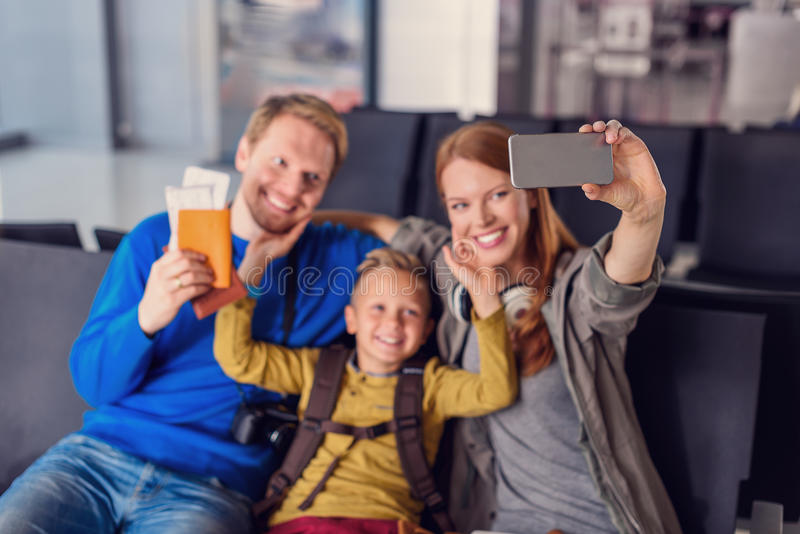 Family waiting for departure at airport. Vacation time rocks. Smiling beautiful taking selfie with smartphone while waiting for their flight at airport stock image
