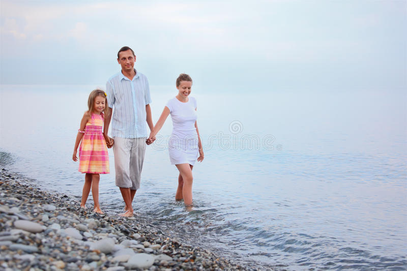 Family walk on beach in evening, focus on mother royalty free stock photography