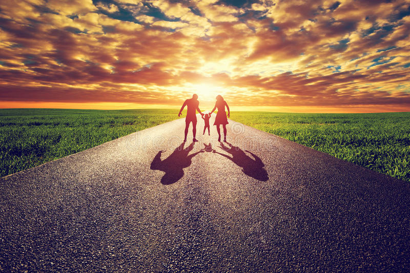 Family walk on long straight road, way towards sunset sun royalty free stock image
