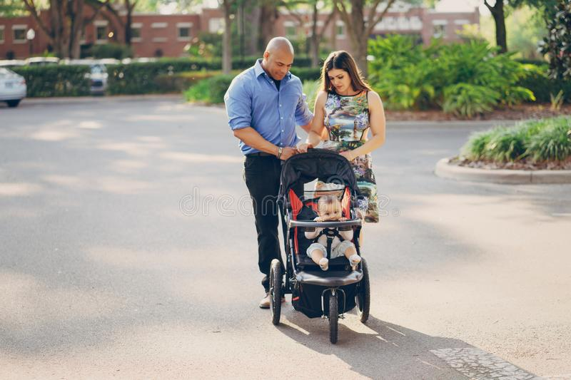 Family on a walk. Mom and dad a wonderful little son walking in summer sunny city royalty free stock photo