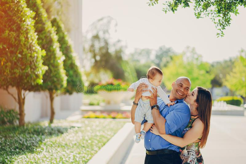 Family on a walk. Mom and dad a wonderful little son walking in summer sunny city royalty free stock photography