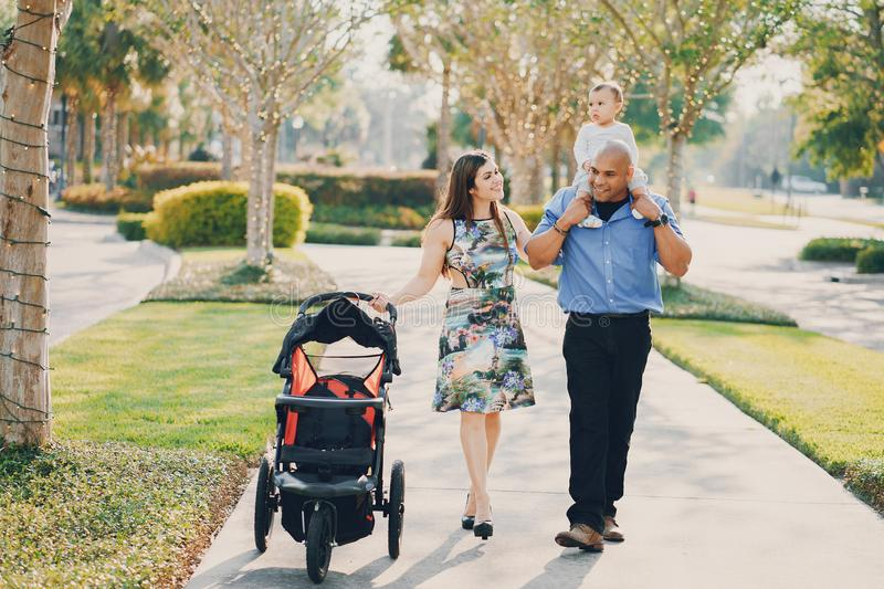 Family on a walk. Mom and dad a wonderful little son walking in summer sunny city stock image