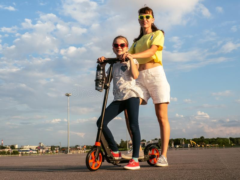Family walk: Mom and daughter in sunglasses and summer clothes ride to the scooter. royalty free stock photo