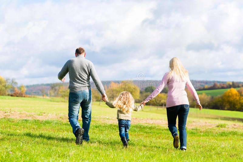 Family walk through the park in fall stock image