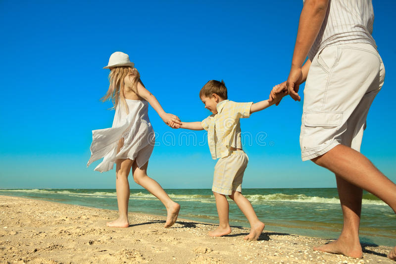 Family walking along the beach. While on vacation stock photo