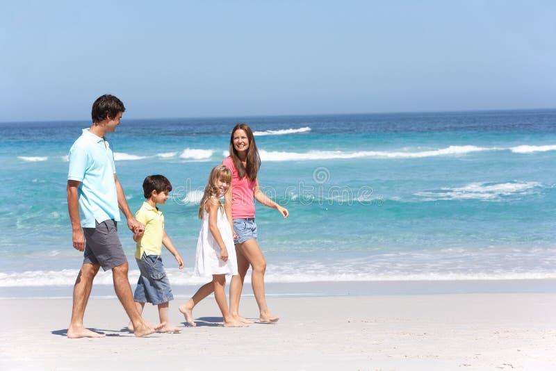 Family Walking Along Sandy Beach royalty free stock photography