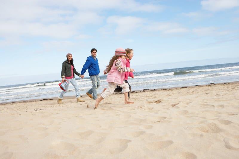 Family Walking Along Winter Beach royalty free stock image