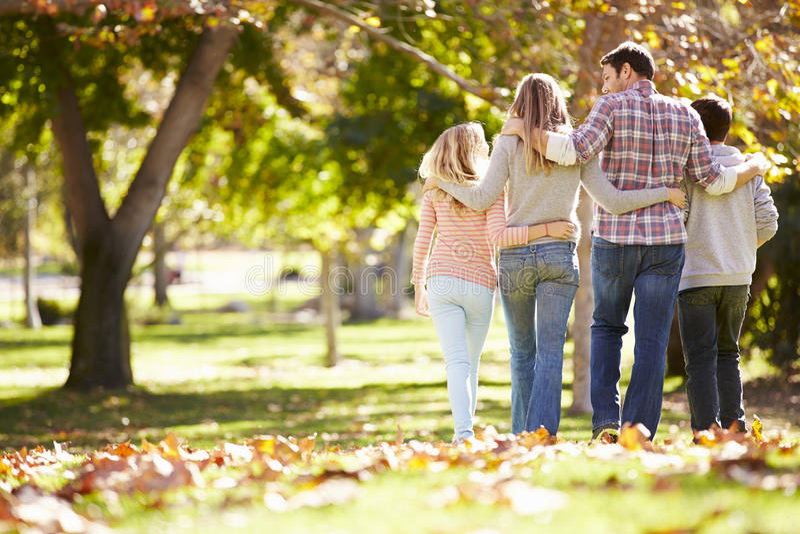 Family Walking Through Autumn Woodland stock photo