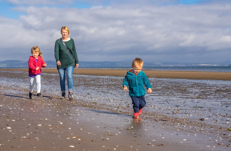 Family walking on the beach stock photography