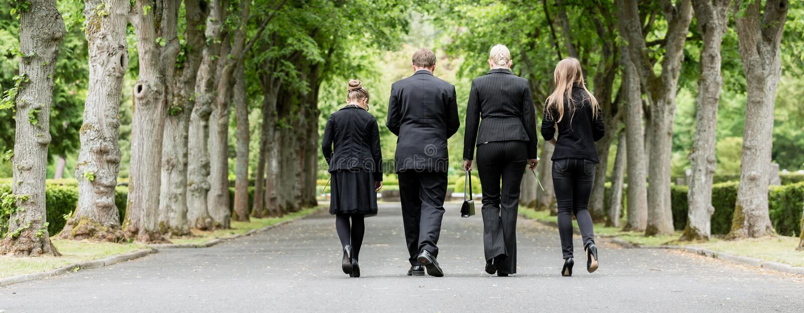 Family walking down alley at graveyard. Mourning family walking down alley at graveyard royalty free stock photo
